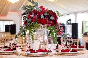 red flower decoration in clear vase - wedding table decoration