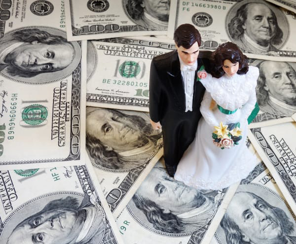 Wedding Budget - Bride And Groom Figurines On Hundred Dollar Bills