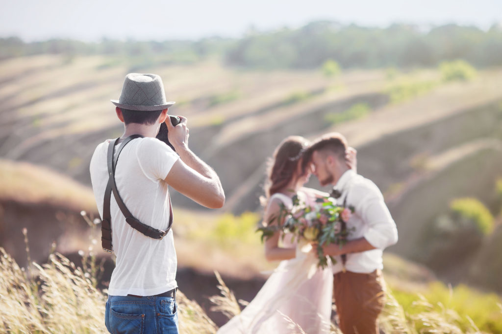 Wedding Photographer - Man Photographing Couple Outside