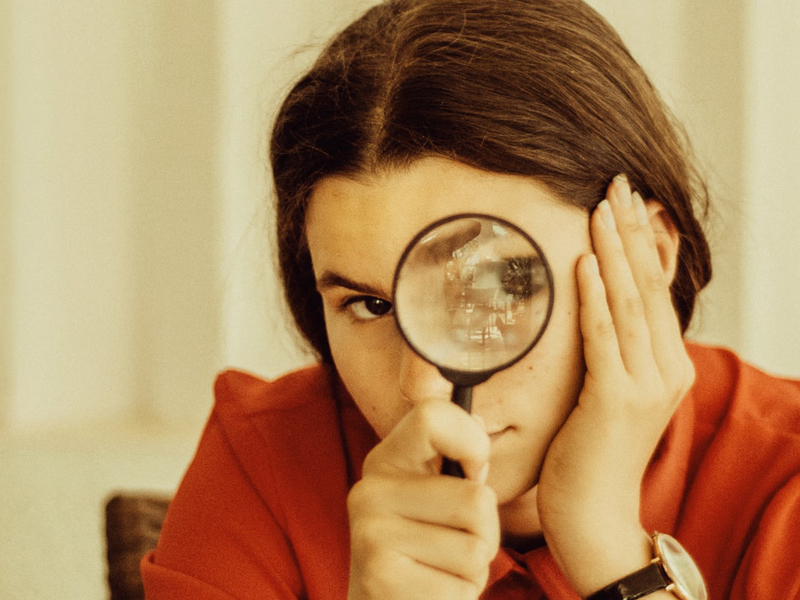 Brunette Woman With Magnifying Glass