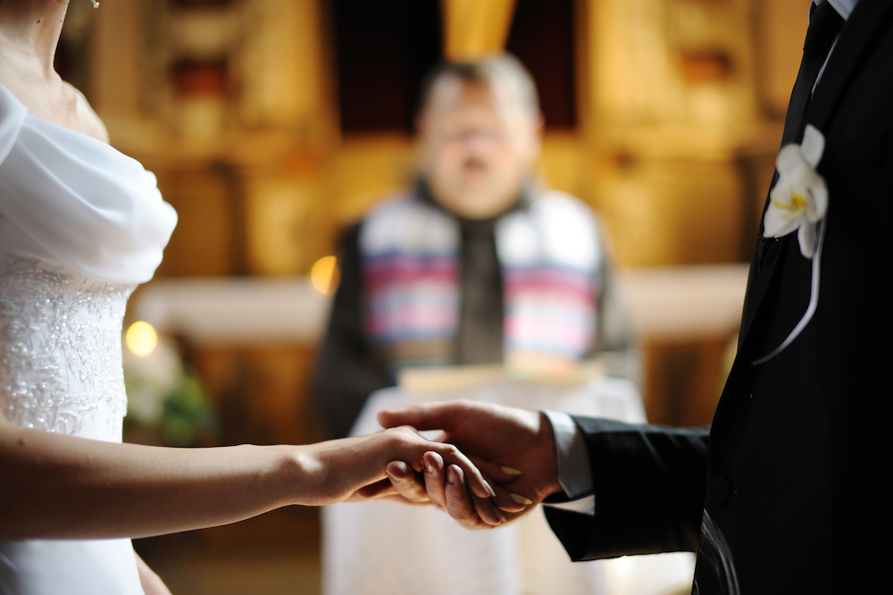 Bride and groom holding hands at church.