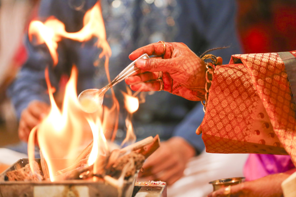 Putting spoon in fire during Indian wedding tradition.